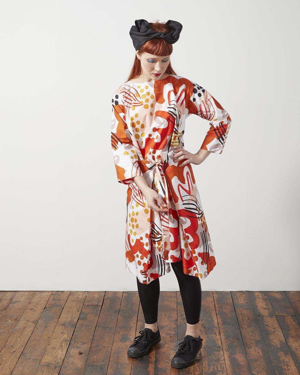 Woman wearing colourful patterned dress by Georgia Boniface
