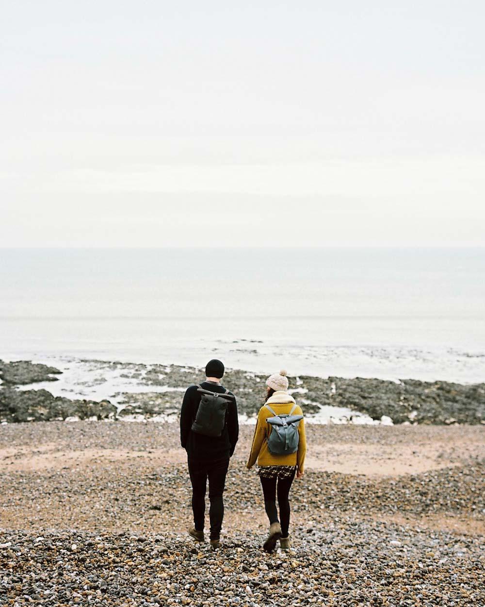 Couple on beach wearing Millican backpacks