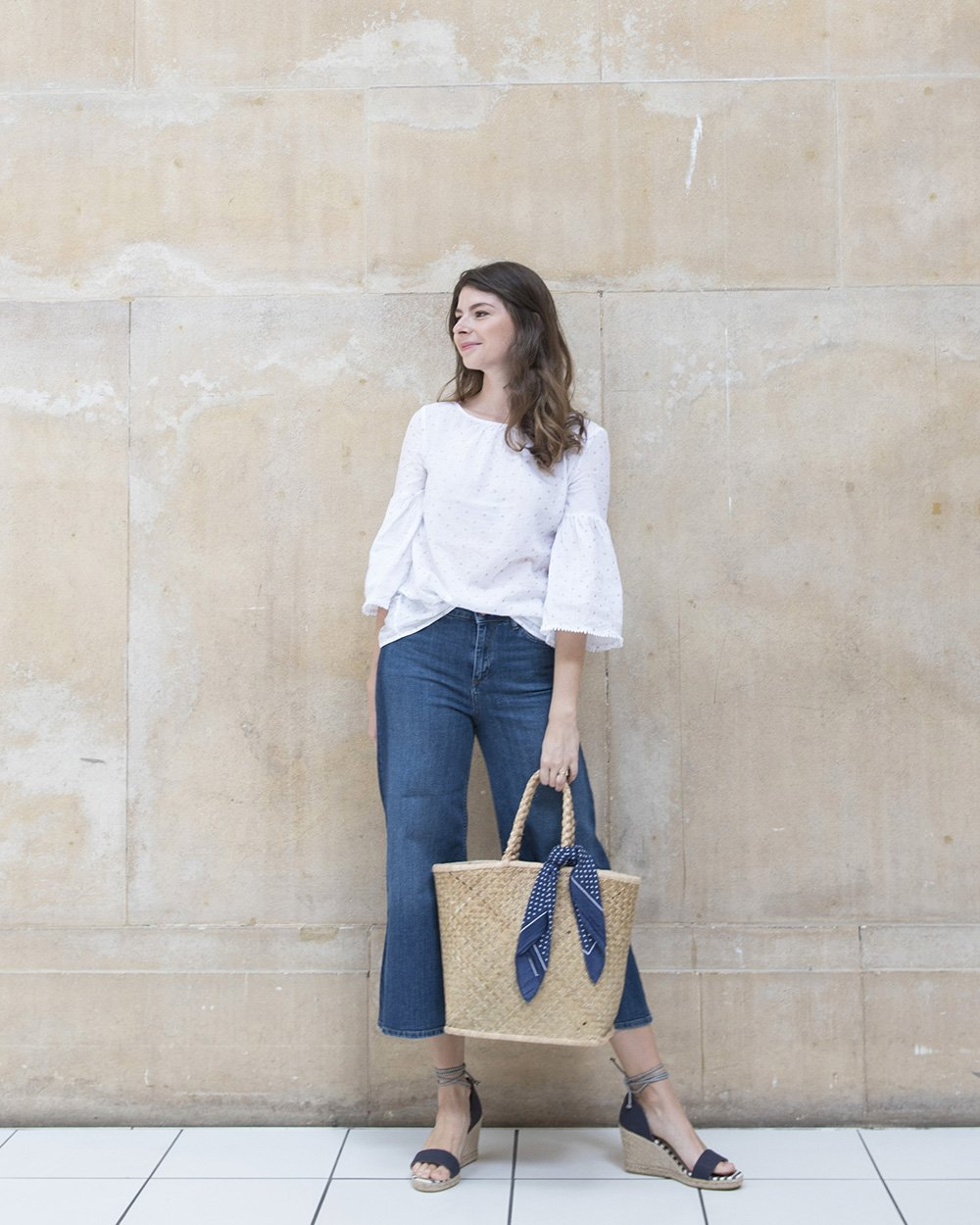 Stylist Nancy Straughan posing against a concrete wall wearing white top and blue jeans, holding a basket bag
