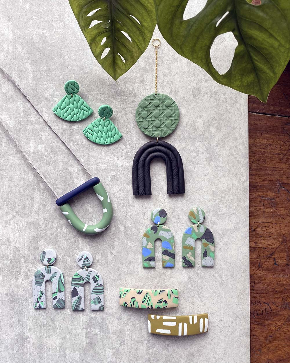 Overhead selection of colourful blue and green Fison Zair polymer clay jewellery